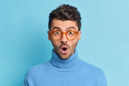 Close up portrait of shocked unshaven Caucasian man keeps mouth opened reacts on something breathtaking being startled stares through glasses weas casual turtleneck isolated on blue background