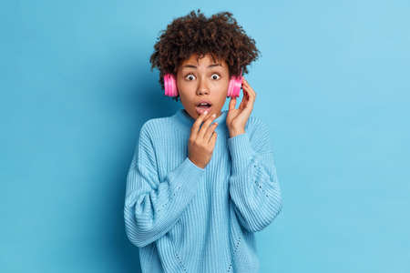 Speechless dark skinned young Afro American woman has impressed face expression wears stereo headphones keeps mouth opened dressed in oversized knitted sweater isolated over blue background.