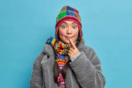 Wondered ethnic girl looks surprisingly at camera keeps index finger near lips wears warm winter clothes hears something embarrassing going to have walk outdoor during frosty weather. Inuit woman