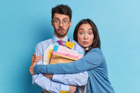 Emotional shocked woman and man partners stare stunned at camera meet to discuss working plan study project together. Scared Asian female embraces groupmate afraid of passing exam. Two colleagues