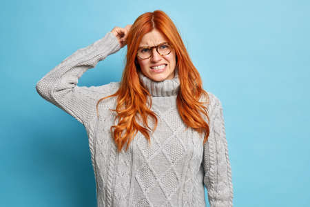 Young puzzled ginger woman scratches head clenches teeth and looks with dissatisfaction at camera tries to solve problem or remember something important has bad memory poses indoor over blue wall Foto de archivo