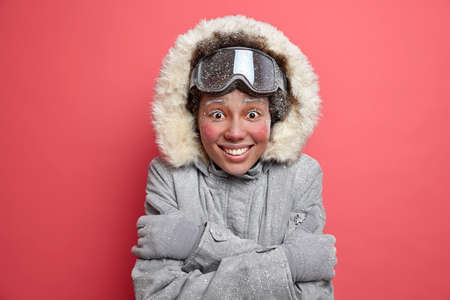 Photo of joyful woman with red cheeks covered by hoarfrost embraces herself wears warm thermo jacket poses against pink background shivers as spends time outdoor during severe cold or frost.