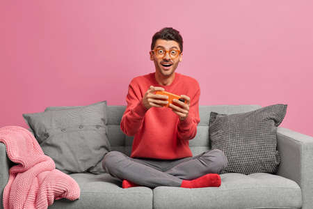 Technology internet and gaming concept. Excited Caucasian man plays racing game on smartphone looks surprisingly at camera dressed casually poses on comfortable sofa against pink background.