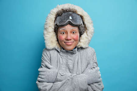 Winter holidays and recreation concept. Cheerful frozen woman feels cold after going snowboarding in mountains trembles and hugs herself to warm wears grey jacket with hood gloves feels satisfied