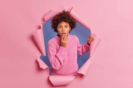 Speechless astonished woman stands in torn pink paper background keeps jaw dropped reacts on amazing sales notices unbelievable thing wears warm sweater. Breaking on. Human reactions concept.