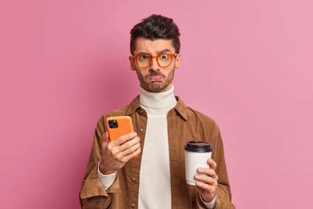 Sad unsaven man purses lips and looks unhappily at camera holds smartphone reads offensive comments under his post drinks aromatic coffee from disposable cup wears optical glasses and shirt.