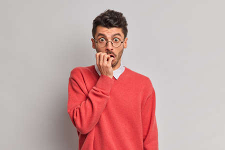 Shocked nervous man bites finger nails stares through optical glasses dressed in red jumper isolated over grey background. Young European guy afraids of something terrifying poses anxious indoor