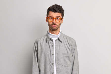 Upset offended man purses lips looks disappointed at camera expresses negative emotions stands discontent against grey background dressed in shirt wears transparent eyeglasses. Face expressions