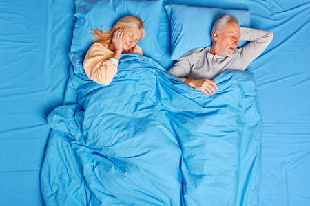 Senior woman cannot stand husband snore covers ears has insomnia. Mature married family couple have nap in comfortable bed under blue blanket. Getting peaceful night of rest. Having good rest at home