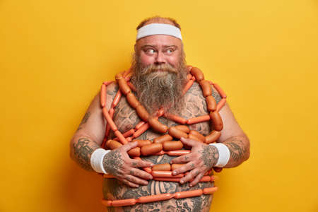 Plump bearded man with big tattooed belly wears headband and wristbands stands wrapped by sausages tries to loose weight isolated over yellow background. Stout overweight guy has bad eating habits Foto de archivo