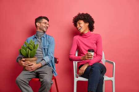 Horizontal shot of happy multiethnic woman and man have pleasant talk look at each other and pose on chairs against pink background. Glad Afro American woman drink coffee European man drinks coffee