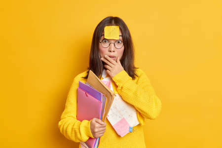 Photo of puzzled surprised Asian female student has memo note stuck on forehead prepares coursework carries folders with papers makes education project works at her assignment studies remotely