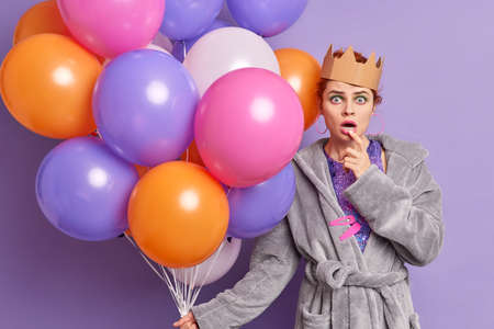 Impressed female model stares bugged eyes at camera feels surprised holds colorful inflated balloons dressed in domestic gown going to celebrate something isolated over purple studio background.
