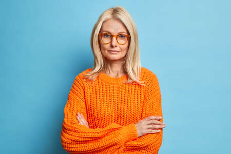 Portrait of beautiful serious middle aged woman keeps hands crossed wears spectacles and orange sweater looks confidently at camera listens attentively interlocutor isolated over blue background