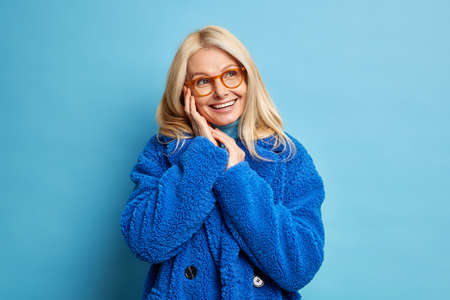 Portrait of forty years old woman with blonde hair brilliant toothy smile keeps hands near face looks happily aside has dreamy expression wears winter coat in one tone with background. Fashion concept
