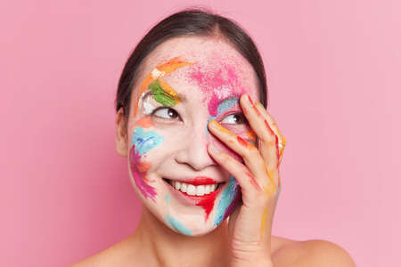 Close up shot of womans face smeared with colorful acrylic paints smiles broadly stands shoulders isolated over pink background. Happy professional female artist has creative makeup. Bright style