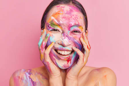 Headshot of happy brunette woman has face stained with colorful stains smiles broadly has white teeth keeps hands on cheeks isolated over rosy background. New creative makeup. Holi festival of colors