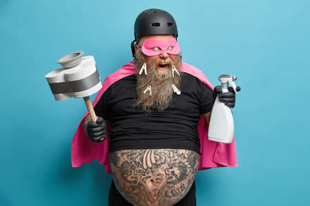 Positve bearded plump man does domestic chores cleans everything in house wears black undersized t shirt rubber gloves helmet holds plunger and detergent isolated over blue wall. Super hero indoor
