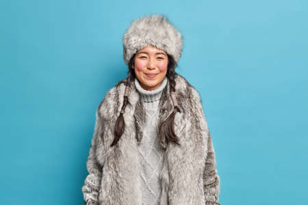 Pleased young Eskimo woman has rouge cheeks from frost two long pigtails dressed in sweater fur coat and hat adapted to cold weather isolated over blue studio background. Northern inhabitant