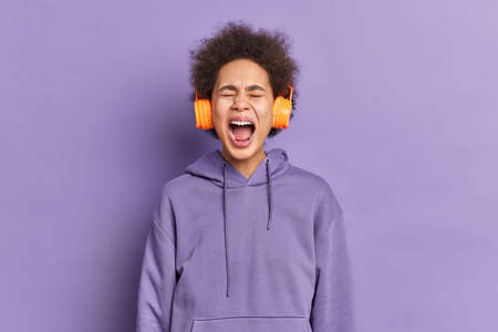Studio shot of emotional Afro American woman shouts loudly keeps mouth opened dressed in hoodie isolated over purple background listens favorite music via headphones. Negative emotions lifestyle Stock Photo