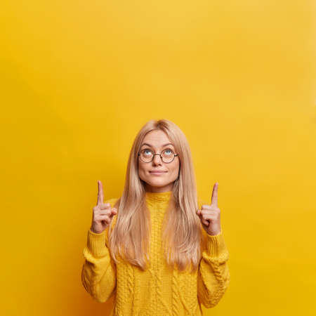 Good looking blonde woman indicates both index fingers upwards shows amazing offer dressed in casual sweater isolated over yellow background. Look at this promotion. Use copy space for your advert