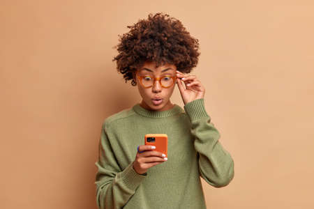 Photo of speechless impressed dark skinned curly beautiful woman stares at smartphone stands with bugged eyes keeps hand on rim of spectacles wears casual jumper has shocked expression reads news.
