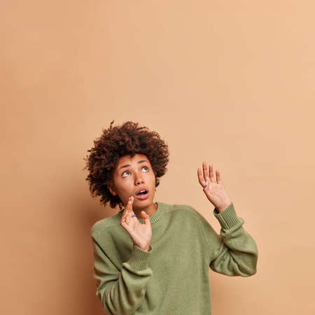 Frightened African American woman keeps arms raised tries to stop something falling above concentrated upwards being afraid wears casual jumper poses against beige background copy space area