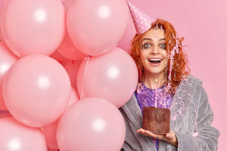 Happy ginger young woman with surprised glad expression has leaked makeup being on graduation party shocked to get unexpected present holds bunch of airballoons isolated over rosy background