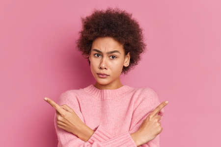 Serious African American woman with curly hair crosses hands and points at different sides hesitates between two items wears casual sweater isolated over pink background. Hard decision concept