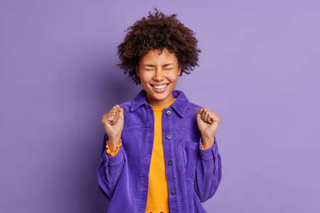Positive overjoyed young Afro American woman raises clenched fists celebrates something with triumph dressed in fashionable jacket isolated over purple background. Yes I finally gained my goal