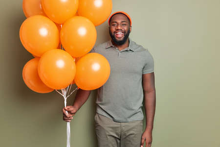 Happy dark skinned Afro American man stands glad dressed in casual clothes holds bunch of orange inflated balloons poses indoor against khaki background. Celebration party and holidays concept.