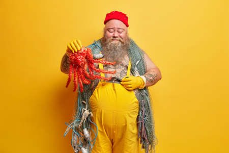 Happy bearded man mariner stands with closed eyes holds red octopus smokes pipe wears red hat and overalls carries fishing net on shoulders isolated over yellow background. Fisherman with sea creature