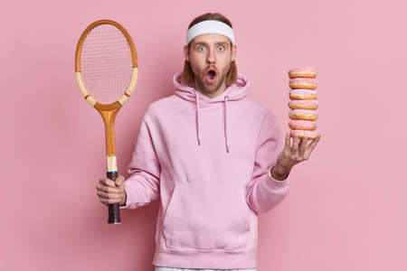 Bearded shocked hipster wears sport outfit holds tennis racket and pile of sweet doughnuts gazes surprisingly at camera with widely opened mouth has active leisure poses against pink background