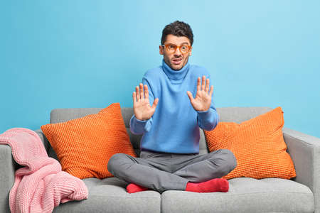 Displeased man sits crossed legs on comfortable sofa makes refusal gesture asks not to bother him keeps palms forward camera dressed in casual clothes poses in living room against blue wall.