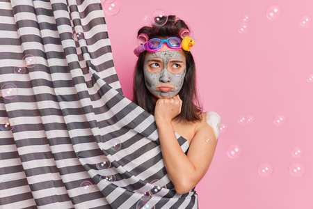Morning routine and hygiene concept. Displeased brunette young Asain woman applies clay mask on face undergoes beauty procedures takes shower poses behind curtain isolated over pink background