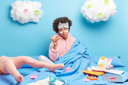 Beautiful dark skinned young woman with curly hair makes little gesture dressed in nightwear wrapped in blanket poses on bed drinks coffee isolated over blue background white fluffy clouds above.