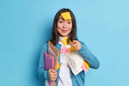 Pleased Asian woman office worker with pleased expression holds folders prepares research work makes reminding notes indicates directly at camera wears casual jumper isolated over blue background