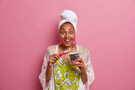 Cheerful surprised dark skinned attractive woman stares surprisingly at camera smiles broadly eats delicious ice cream wears wrapped towel on head poses against pink background spends time at home Фото со стока