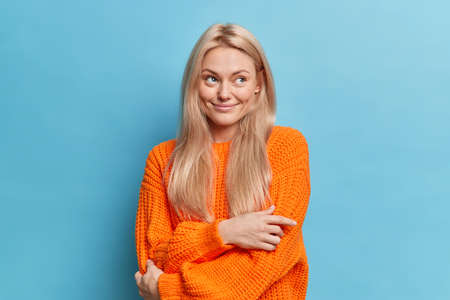 Indoor shot of dreamy blonde young woman embraces herself contemplates about something pleasant dressed in orange knitted sweater isolated over blue background. I will think for some minutes Stock fotó
