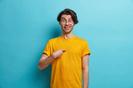 Do you mean me. Cheerful Caucasian man points at himself looks surprisingly at camera surprised being mentioned by someone wears round spectacles and yellow t shirt isolated over blue background Фото со стока