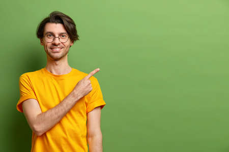 Cheerful Caucasian man points index finger at copy space suggests special offer dressed casually wears round glasses isolated over green studio background. Best choice. Place your advertisement there