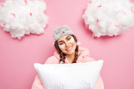 Sleepy time. Positive good looking girl tilts head smiles gently wears nightwear applies collagen patches under eyes wishes sweet dreams holds soft pillow isolated over pink background with clouds