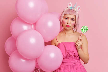 Unhappy Asian woman with bob rosy hairstyle wears festive dress holds lollipop and balloons upset with something isolated over pink background. Bad emotions celebration holiday event concept
