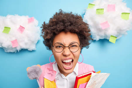 Close up shot of angry emotional female student has curly hair screams loudly being annoyed of constant studying surrounded with sticky notes isolated over blue background. Education concept.