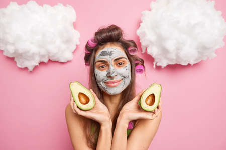 Personal care facial treatment daily pampering routines concept. Pleased brunette young woman applies hair curlers nourishes skin with fresh mask shows avocado pieces poses against pink background