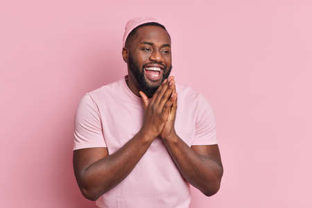 Positive dark skinned man keeps palms together has faith in something good being amused feels happy smiles broadly dressed in casual clothes believes something good happen isolated on pink wall