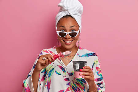 Good looking dark skinned woman smiles happily eats delicious ice cream during hot summer day wears sunglasses dressing gown and towel on head isolated over pink background. Domestic style concept Stock fotó