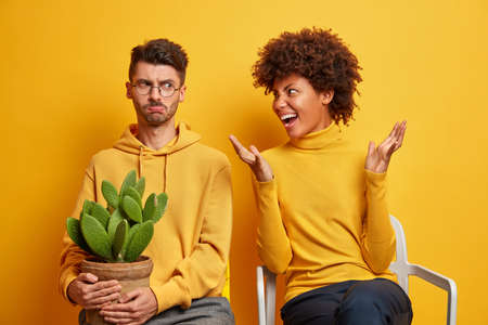 Mixed race couple arguing. Angry annoyed Afro American woman shouts loudly at husband sort out relationships at home pose on chairs over yellow wall. Sad frustrated man has misunderstanding with wife