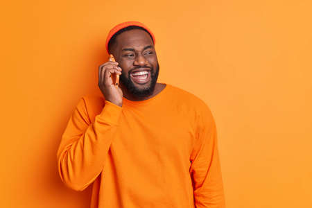 Pleasant conversation concept. Cheerful bearded dark skinned guy makes phone call smiles broadly has white teeth dressed in orange sweater and hat looks aside happily discusses plans for weekends