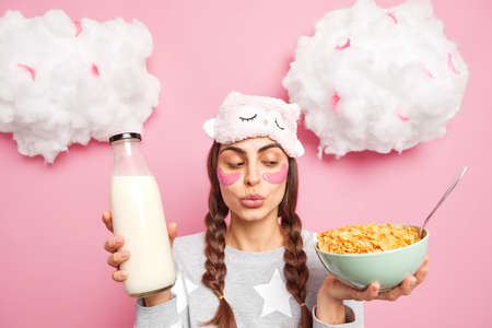 Adorable girl has two pigtails keeps lips folded looks at cornflakes in bowl holds glass bottle of milk going to have breakfast wears comfortable pajama and blindfold reduces wrinkles under eyes